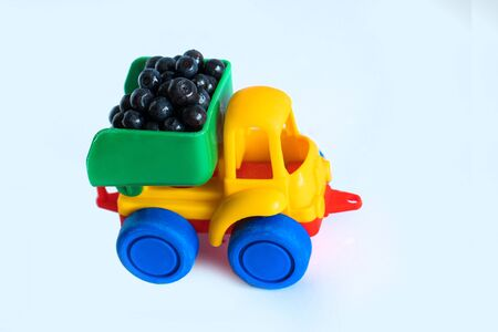 raspberry natural vitamins are in the back of truck in a childrens toy car food delivery truck logistics Stock Photo - 126079983
