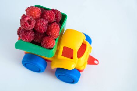 raspberries natural vitamins are in the back of truck in a childrens toy car food delivery truck logistics Stock Photo