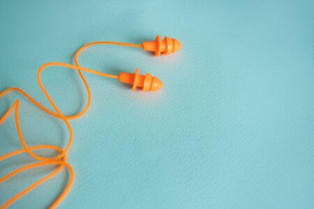 pair of orange rubber earplugs in the form of spruce lie on a blue background