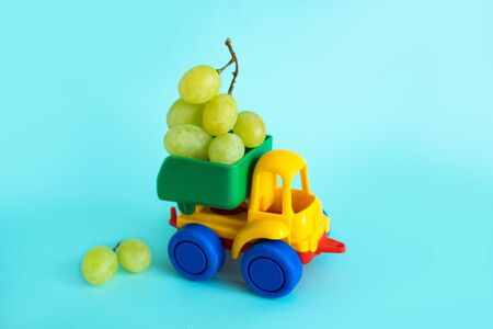 grapes natural vitamins are in the back of truck in a childrens toy car food delivery truck logistics