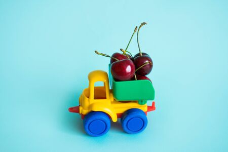 cherries natural vitamins are in the back of truck in a childrens toy car food delivery truck logistics Stock Photo