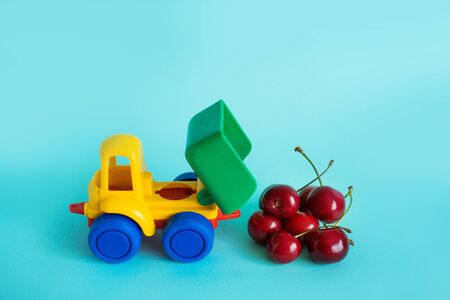 cherries natural vitamins are in the back of truck poured out in a childrens toy car food delivery truck logistics