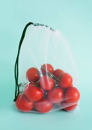 A ripe branch of cherry tomato lies in reusable reuse bag on an isolated blue background. to deal with disposable plastic bags Stock Photo - 127369608