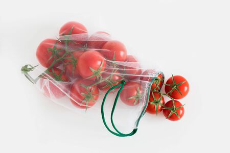 A ripe branch of cherry tomato lies in reusable reuse bag on an isolated white background. to deal with disposable plastic bags Stock Photo