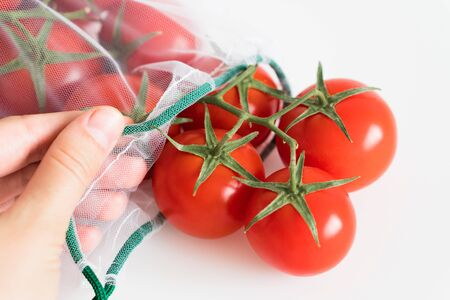 female hand touches ripe branch of cherry tomato lies in reusable reuse bag on an isolated white background. to deal with disposable plastic bags Stock Photo