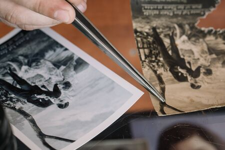 Belarus, Soligorsk, July 1, 2019: mastery of restoring old vintage damaged photos of close-up specialist working place with a pair of tweezers