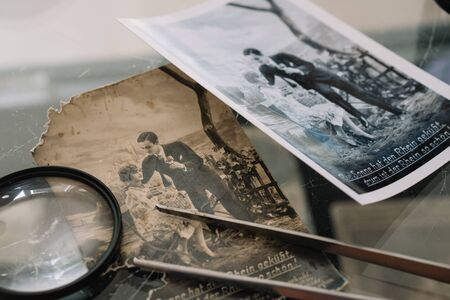 Belarus, Soligorsk, July 1, 2019: mastery of restoring old vintage damaged photos of close-up specialist working place with a pair of tweezers with a magnifying glass