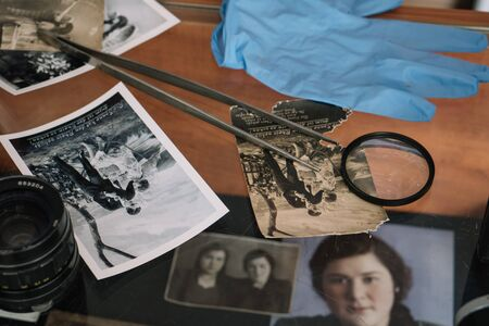 Belarus, Soligorsk, July 1, 2019: mastery of restoring old vintage damaged photos of close-up specialist working place with a pair of tweezers with a magnifying glass and gloves