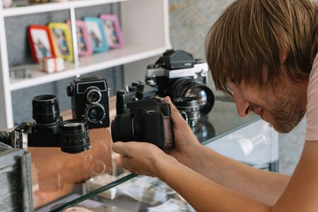 young male photographer takes photographs with modern digital camera old retro analog film cameras in a shop photo showcase collection