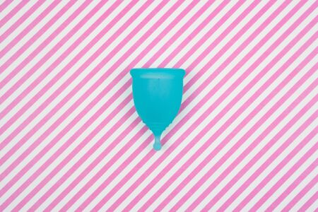 menstrual cup on a pink striped background. feminine hygiene during period time, top view