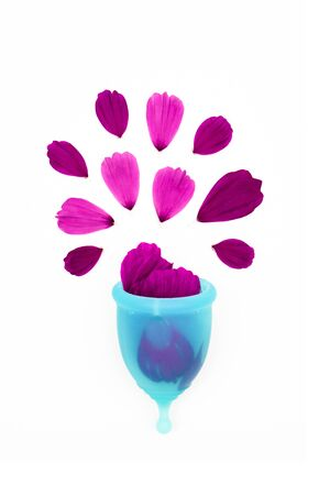 woman personal hygiene item for period, a blue menstrual cup filled with flower petals, like metaphor of a drop of blood splashing overflowed on a white background