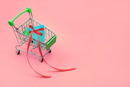 blue menstrual cup with a red bow as bonus or gift in a mini Supermarket Trolley on a pink isolated background Standard-Bild - 129169309