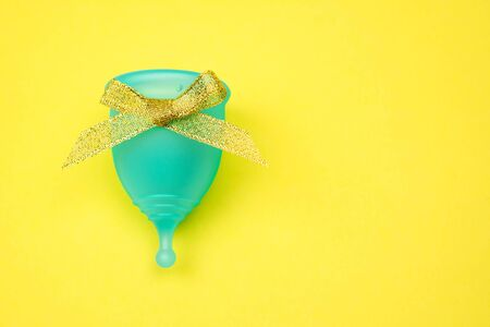 blue menstrual cup with gold bow as a gift on a yellow background. feminine hygiene in the period, top view, top view