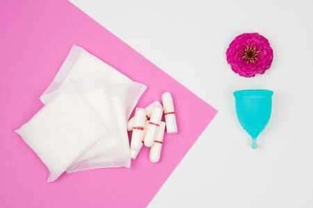 female personal hygiene products isolated on white background blue menstrual cup and swabs pads on a pink background as a choice eco-friendly zero waste reusable product for a period of time