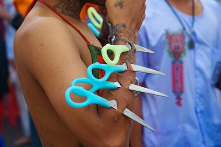 Thailand, Phuket, October 7, 2019: close-up shot of Thai mans hand piercing the skin on his hand with daggers similar to the tip of a pair of scissors at a celebration of the Vegetarian Festival 報道画像