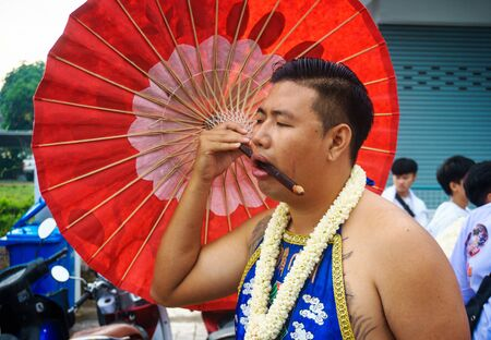 Thailand, Phuket, October 7, 2019: close-up portrait of a Thai man of Chinese descent with a pierced cheek pierced by a large Chinese red umbrella at the annual Phuket Vegetarian Festival 報道画像