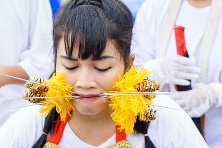 Thailand, Phuket, October 7, 2019: portrait of a young beautiful Thai girl of Chinese descent with a pierced metal knitting needle on her cheek at celebration of a festival of vegetarians 報道画像