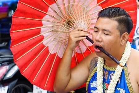 Thailand, Phuket, October 7, 2019: close-up portrait of a Thai man of Chinese descent with a pierced cheek pierced by a large Chinese red umbrella at the annual Phuket Vegetarian Festival, copy space