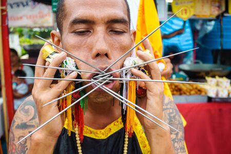 Thailand, Phuket, October 7, 2019: close-up portrait of a Thai man of Chinese descent with pierced cheek pierced by a lot of metal knitting needles at the annual festival of Vegetarianism in Phuket Town