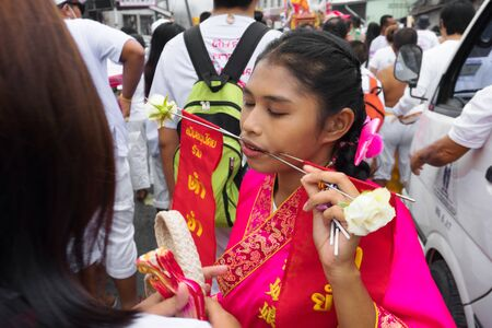 Thailand, Phuket, October 5, 2019: Closeup portrait of a young beautiful Thai girl of Chinese descent with a pierced metal knitting needle on her cheek at celebration of a festival of vegetarians