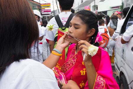 Thailand, Phuket, October 5, 2019: portrait of a young beautiful Thai girl of Chinese descent with a pierced metal knitting needle on her cheek at celebration of a festival of vegetarians 報道画像