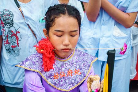 Thailand, Phuket, October 7, 2019: Closeup portrait of a young beautiful Thai girl of Chinese descent with a pierced metal knitting needle on her cheek at celebration of a festival of vegetarians 報道画像