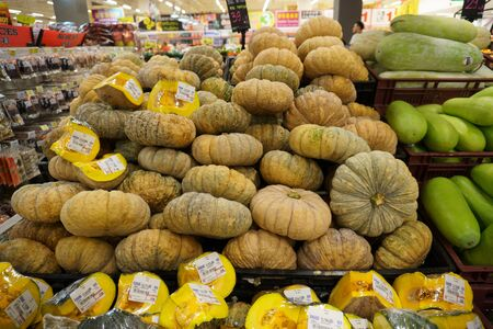 group of pumpkins pale gloomy color are lying tightly on a stand in a supermarket in the vegetable department, buyers in the background are blurred