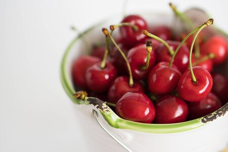 Ripe red cherry in a white garden enamel bucket with a green border on a white background close-up 写真素材