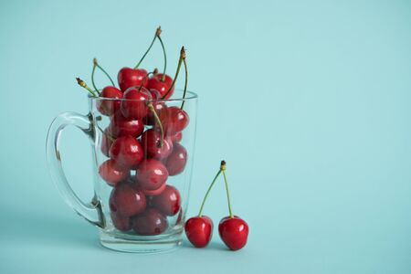 ripe cherries in a glass transparent mug on a bright contrasting blue turquoise background next to a eyelid with berries 写真素材