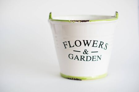 white garden bucket with a green border and a wooden handle on a white fna isolated Фото со стока