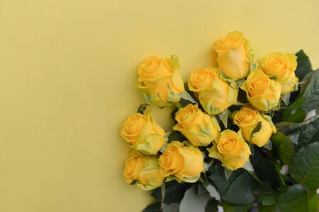 A bouquet of fresh yellow roses flowers with leaves on an isolated background. Flat lay, top view. corner composition. postcard birthday floral arrangement