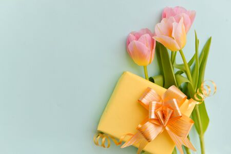 bouquet of delicate pink tulips and a yellow box gift with a bright bow on an isolated blue background, floral festive arrangement of flowers, gold candy paillettes against the background