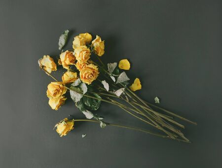 A dry bouquet of yellow roses on a black background, frustration at the end of the holidays, a sad day, toned faded faded image stylized retro