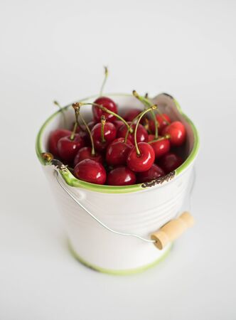 Ripe red cherry in a white garden enamel bucket with a green border on a white background