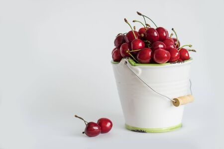 Ripe red cherry in a white garden enamel bucket with a green border on a white background copy space