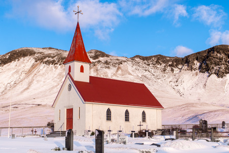 A traditional icelandic church stands proud at the foot of a small mountain, in southern Iceland