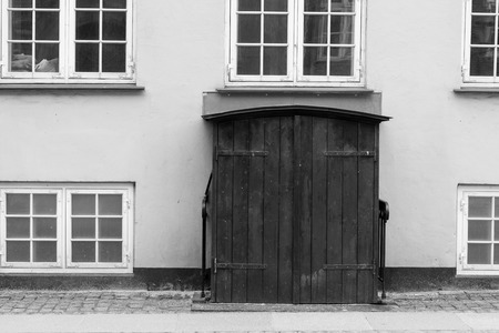 A double doorway photographed in black and white. Windows surround the portal, with one window containing a pile of papers 写真素材