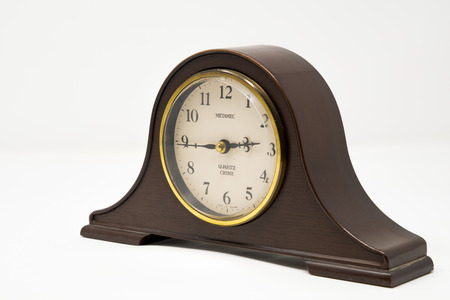 A traditional mantel clock with gold accents photographed against a white background