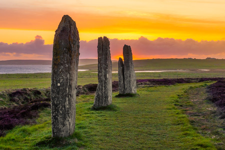 Theree standing stones of the ancient and mysterious Ring of Brodgar underneath a dramatic sunset 免版税图像