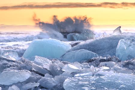 The sun rises over the Atlantic Ocean illuminating the famous Icebergs on Diamond Beach, at the opening of Jökulsárlón glacier lagoon