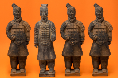 4 isolated Chinese terracotta warriors against a bright orange background