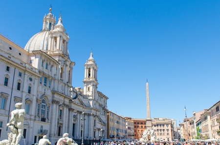 The Egyptian Obelisk in Piazza Navona, Rome, with the dome and twin bell towers of the Catholic church, Sant'Agnese in Agone to the left. A dove adornes the top of the obelisk