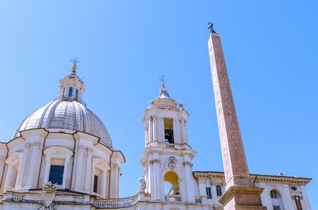 The Egyptian Obelisk in Piazza Navona, Rome, with the dome and bell tower of the Catholic church, SantAgnese in Agone, in the background. A dove adornes the top of the obelisk