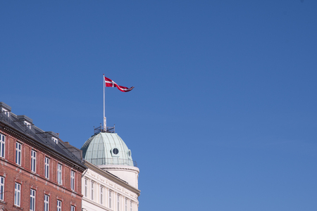 The National Flag of Denmark flies high above a round domed roof on the corner of a white appartment block overlooking Nyhavn in Copenhagen