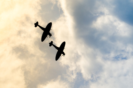 Two silhouetted spitfires dive out of the bright sun, as if attacking an enemy with surprise. Hiding in the sun is an effective and common air fighter tactic to catch their foe off guard Stock Photo
