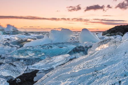 The sun rises over the Atlantic Ocean illuminating the famous Icebergs on Diamond Beach, at the opening of Jökulsárlón glacier lagoon