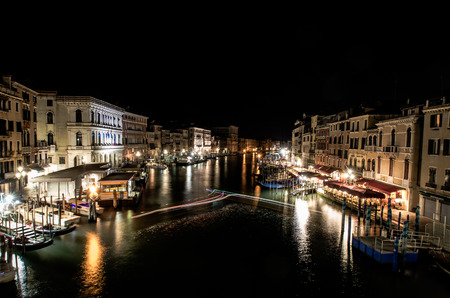 A late night long exposure view of the popular Grand Canal in Venice, taken from the top of the Ponte Rialto Bridge, with a light trail set provided by a boat manoeuvring in the moorings.