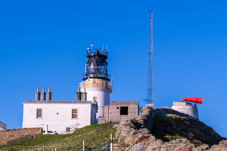 The old lighthouse at Sumburgh Head, on the southern tip of Shetland Isles on a clear blue evening. The red-painted ancient foghorn is still visible, mounted on a concrete pillar and facing East
