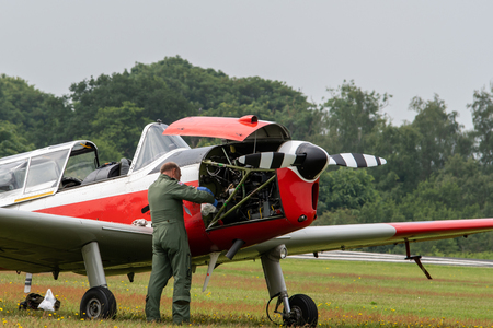TELFORD, UK, JUNE 10, 2018 - A photograph documenting the pilot performing maintenance on a vintage de Havilland Chipmunk aircraft at RAF Cosford