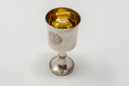 A stirling silver communion chalice to hold the wine during Holy Communion services, with a golden lining and set against a white background